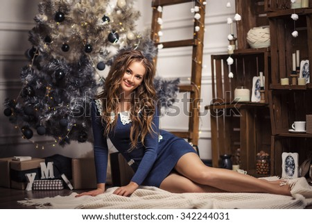 Christmas Gift. New year celebration. Beautiful holdiay decorated room with Christmas tree with presents under it. New Year and Christmas concepts. Beautiful girl sitting near New Year tree.  - stock photo