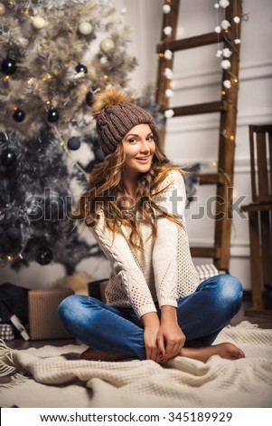 Christmas Gift. New year celebration. Beautiful holidiay decorated room with Christmas tree with presents under it. New Year and Christmas concepts. Beautiful girl sitting near New Year tree. - stock photo