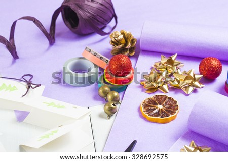 christmas gift packaging with purple papers and cards with christmas tree print - stock photo