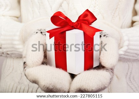 Christmas gift with a red satin ribbon in female hands with mittens - stock photo