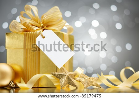 christmas gift with blank tag against bokeh lights background - stock photo