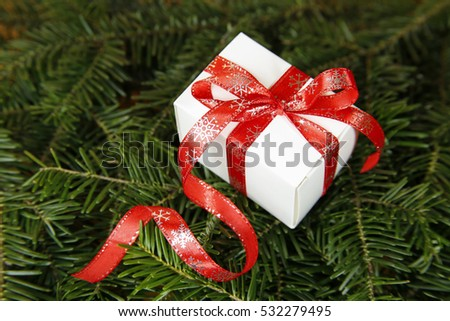 christmas gift with decorative ribbon on fir tree
