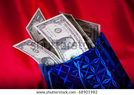 Christmas gift with dollars on red background