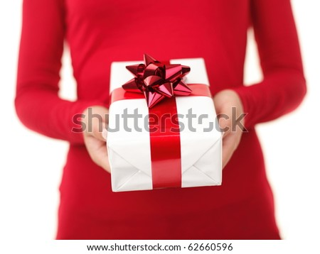 Christmas gift. Woman giving / holding christmas present. Focus on the gift - shallow depth field. unrecognizable person isolated on white. - stock photo