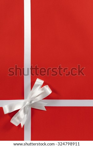 Christmas gift wrap ribbon and bow, red paper background, vertical, copy space - stock photo