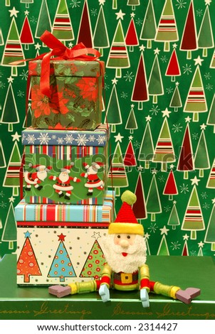 Christmas Gifts - A stack of three wrapped gifts and a Santa toy against a colorful holiday background.