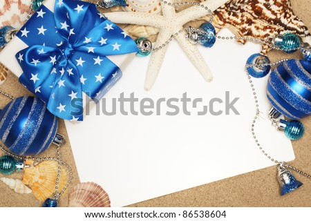 Christmas gifts and blank card on sand beach,closeup. - stock photo