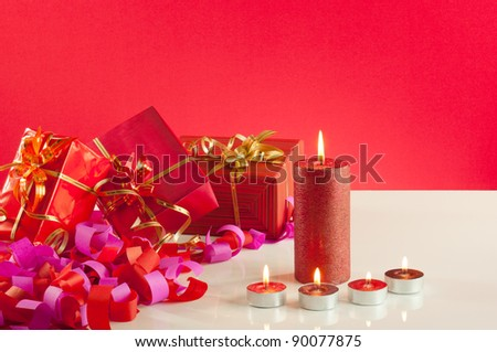 Christmas gifts and candles over red background - stock photo
