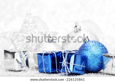 Christmas gifts and decoration on shiny silver glitter background