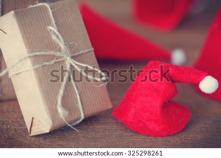 christmas gifts and santas hat on wooden board - stock photo