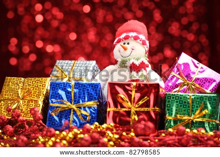 Christmas gifts and snowman over abstract light background. - stock photo