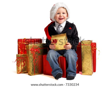 Christmas gifts for little one. Studio shot of happy cute boy in Santa hat with a lot of packed gifts - stock photo