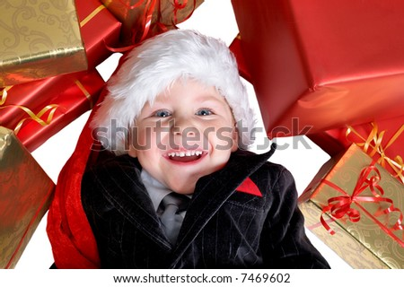 Christmas gifts for little one. Studio shot of happy cute boy in Santa hat with a lot of packed gifts