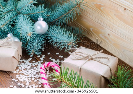christmas gifts in craft paper, pink candy cane, sprinkling as snowflakes  on wooden table. Christmas tree with silver and golden balls. - stock photo