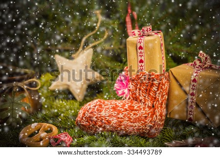 Christmas gifts in handsewn socks. Christmas decorations in the branches of spruce - stock photo