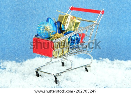 Christmas gifts in shopping trolley, on blue shiny background