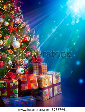 Christmas gifts near the Christmas tree in a magical Christmas Eve - stock photo