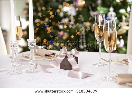 Christmas gifts on the beautiful table with Christmas tree on background. Holidays and celebration concept