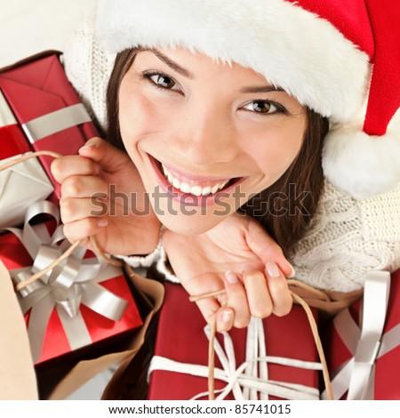 Christmas gifts santa woman shopping. Closeup portrait of young woman holding christmas presents in shopping bags. Beautiful smiling happy santa girl wearing santa hat. - stock photo