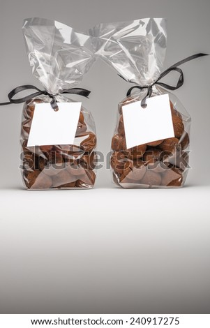 Christmas gifts. Two luxury plastic bags with black ribbons of chocolate truffles and copy space. Blank label  that you can add your own trademark or your own message. Shooting on grey background - stock photo