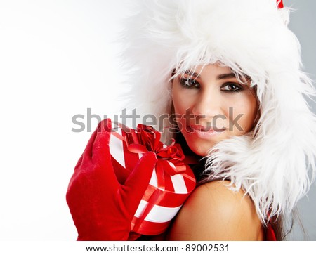 Christmas gifts. Woman wrapping christmas presents wearing santa hat. - stock photo
