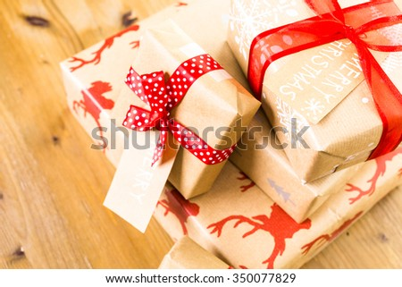 Christmas gifts wrapped in brown paper with red ribbons.