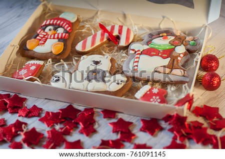 Christmas gingerbread cookie figures of snowman, penguin, seal, boot, mitten laying in box near red decorative stars, balls on wooden table