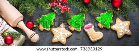 Christmas gingerbread cookies and decorations on a dark slate background. Long banner format.