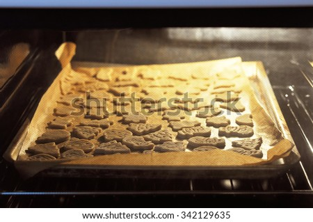 Christmas gingerbread cookies being baked in oven