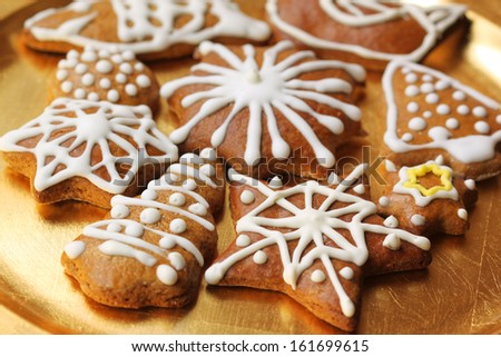 Christmas gingerbread cookies on golden plate. White icing decoration - stock photo