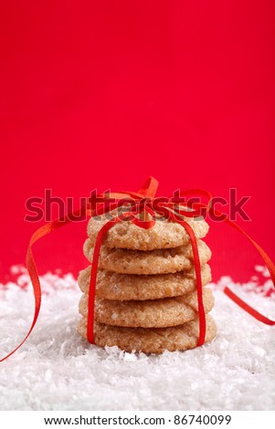 Christmas gingerbread cookies tied with red ribbon on the snow - stock photo