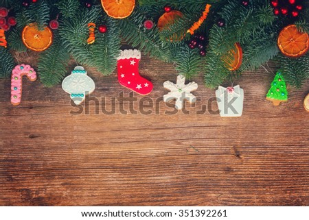 christmas gingerbread cookies with fir tree border on wooden background, retro toned - stock photo