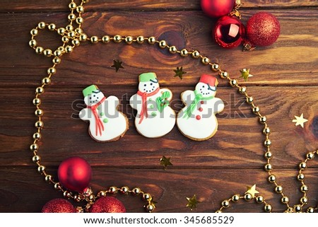 Christmas gingerbread cookies with three snow mans on wooden background with Christmas balls. Top view. Shallow depth of field.