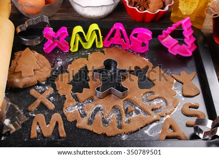 christmas gingerbread dough and cookie cutters on black tray with ingredients and utensils - stock photo