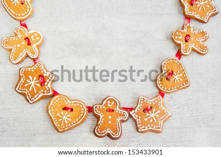 Christmas gingerbread figures hanging on a red ribbon on a wooden background - stock photo