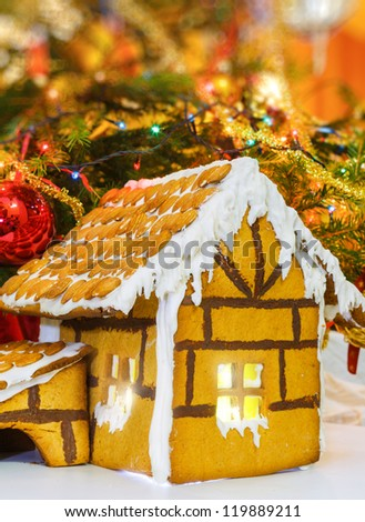 Christmas gingerbread house decoration on background of defocused christmas tree. Hand decorated. Vertical view - stock photo