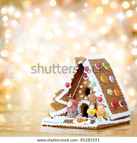 Christmas gingerbread house decoration on background of defocused golden lights. Hand decorated. Shallow DOF. - stock photo