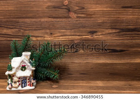 Christmas gingerbread house near the fir branches and Christmas balls on a wooden background with space for text - stock photo