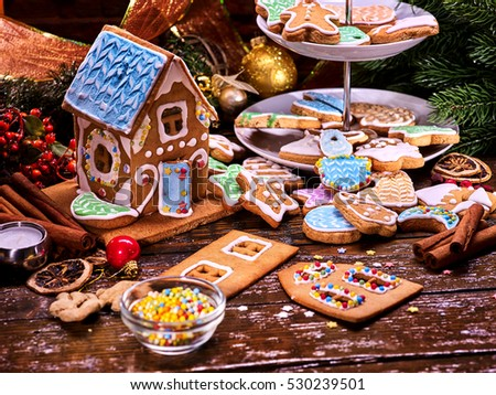 Christmas gingerbread house. Parts of the gingerbread house. Christmas cookies and Christmas balls, candles. Small edible beads for decorating cakes. Spruce branches for decoration. Child development.