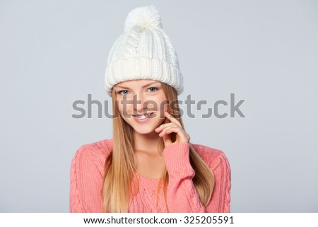 Christmas girl, Closeup portrait of young beautiful smiling woman wearing warm winter clothing, over grey background - stock photo