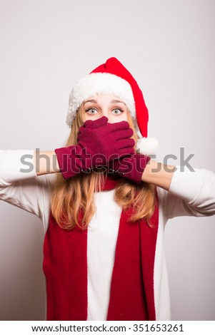 Christmas girl covers her mouth with her hands for a surprise on a gray background. Santa hat isolated portrait of a woman.