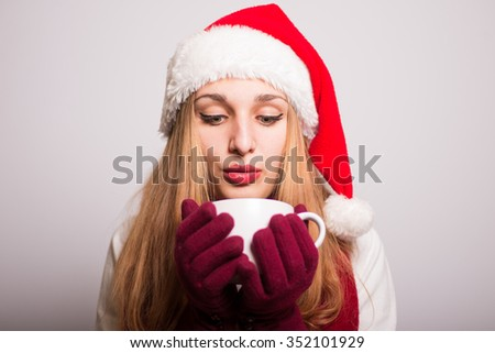Christmas girl drinking tea to keep warm in winter. Santa hat isolated portrait of a woman on a gray background. - stock photo