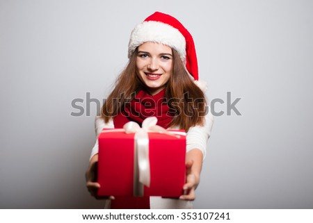 Christmas girl gives a gift. Santa hat isolated portrait of a woman on a gray background.