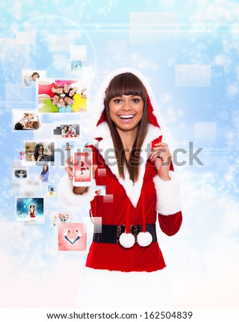 christmas girl happy smile hold cell phone mobile present, woman wear Santa Clause costume show touch screen, new year communication concept over background - stock photo