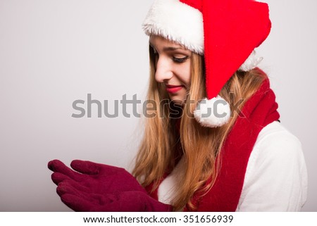 Christmas girl holding a snowflake on a palm. Santa hat isolated portrait of a woman. - stock photo