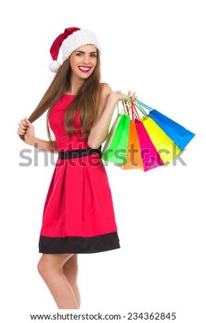 Christmas girl holding colorful shopping bags. Three quarter length studio shot isolated on white. - stock photo