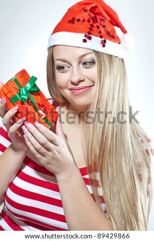 Christmas girl holding gift wearing Santa hat over white background - stock photo