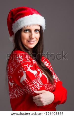 Christmas girl in red sweater over dark background. Studio shot. - stock photo