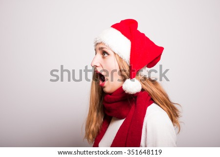 Christmas girl screaming Happy New Year. Santa hat isolated portrait of a woman on a gray background. - stock photo