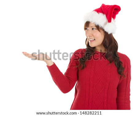 Christmas girl showing empty palm with copy space smile happy standing isolated on white background. Beautiful young smiling woman in red Santa hat showing copyspace.